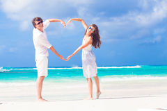 Young happy couple in white making heart shape on Stock Images