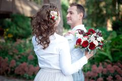 Young happy couple in white shirts having a date outdoor in the forest or park with bouquet of roses royalty free stock photo