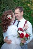 Young happy couple in white shirts having a date outdoor in the forest or park with bouquet of roses stock photos