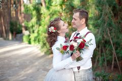 Young happy couple in white shirts having a date outdoor in the forest or park with bouquet of roses royalty free stock image