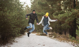 Young happy Couple in Winter Park jumping. Family Outdoors. love Stock Image