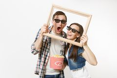 Young happy couple, woman and man in 3d glasses and casual clothes watching movie film on date, holding bucket of royalty free stock image