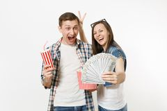 Young happy couple, woman and man watching movie film on date holding bucket of popcorn plastic cup of soda or cola and. Bundle of dollars cash money isolated stock photo