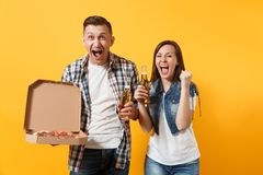 Young happy couple woman man sport fan cheer up support team hold beer bottle italian pizza in cardboard flatbox do. Young happy couple women men sport fan cheer royalty free stock photos