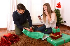Young Happy Couple wrapping Christmas presents Royalty Free Stock Image