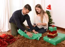 Young Happy Couple wrapping Christmas presents Royalty Free Stock Photos