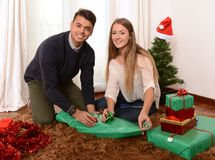 Young Happy Couple wrapping Christmas presents Royalty Free Stock Images