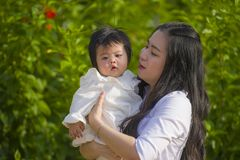 Young happy and cute Asian Chinese woman enjoying and playing with her baby girl daughter holding her smiling cheerful at garden stock images