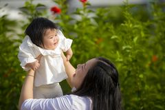 Young happy and cute Asian Chinese woman enjoying and playing with her baby girl daughter holding her raising up in her arms royalty free stock photography