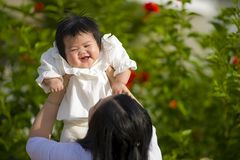 Young happy and cute Asian Chinese woman enjoying and playing with her baby girl daughter holding her raising up in her arms stock photo