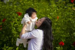 Young happy and cute Asian Chinese woman enjoying and playing with her baby girl daughter holding her raising up in her arms royalty free stock photo