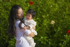 Young happy and cute Asian Chinese woman enjoying and playing with her baby girl daughter holding and kissing her smiling cheerful royalty free stock image