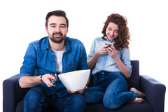 Young happy cute couple sitting on sofa and watching tv isolated. On white background Royalty Free Stock Image