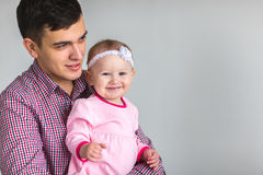 Young happy Dad keeps daughter Stock Photo