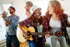 Young happy dancing girls playing guitar and partying. Young beautiful happy dancing girls playing guitar and partying Stock Photos
