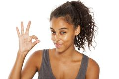 Gesture for delicious. Young happy dark-skinned woman showing gesture for delicious on a white background Stock Photography