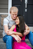 Young happy diverse couple sitting together outdoors Stock Photos