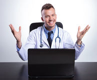 Young happy doctor at his desk welcoming you Royalty Free Stock Images