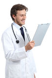 Young happy doctor man reading a medical history. Isolated on a white background Stock Image