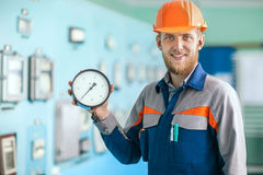 Young happy engineer holding measurement equipment in control ro Stock Photo
