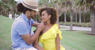 Couple sitting on green grass. Young happy ethnic man and woman looking at each other and sitting on the green grass in the park stock video