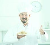 Young happy european cook in cap offering oat porridge for break Stock Images