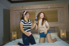 Young happy and excited Asian Chinese girls singing together online karaoke song with microphone and mobile phone jumping at home. On bed as girlfriends having royalty free stock photos
