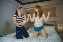 Young happy and excited Asian Chinese girls singing together online karaoke song with microphone and mobile phone jumping at home. On bed as girlfriends having stock image