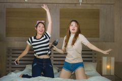 Young happy and excited Asian Chinese girls singing together online karaoke song with microphone and mobile phone jumping at home. On bed as girlfriends having stock photos