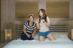 Young happy and excited Asian Chinese girls singing together online karaoke song with microphone and mobile phone jumping at home. On bed as girlfriends having stock images