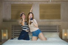 Young happy and excited Asian Chinese girls singing together online karaoke song with microphone and mobile phone jumping at home. On bed as girlfriends having stock photography