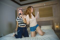 Young happy and excited Asian Chinese girls singing together online karaoke song with microphone and mobile phone jumping at home. On bed as girlfriends having royalty free stock photography