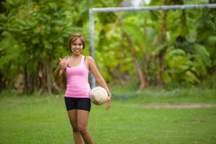 Young happy and excited Asian woman in sport clothes playing football having fun at jungle soccer field with palm trees and grass. In nature and healthy Stock Images