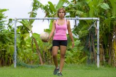 Young happy and excited Asian woman in sport clothes playing football having fun at jungle soccer field with palm trees and grass Royalty Free Stock Images