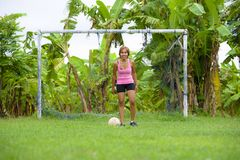 Young happy and excited Asian woman in sport clothes playing football having fun at jungle soccer field with palm trees and grass Royalty Free Stock Photos