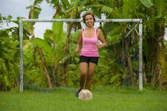 Young happy and excited Asian woman in sport clothes playing football having fun at jungle soccer field with palm trees and grass Stock Image