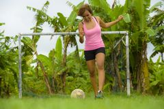 Young happy and excited Asian woman in sport clothes playing football having fun at jungle soccer field with palm trees and grass. In nature and healthy Royalty Free Stock Photos