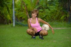 Young happy and excited Asian woman in sport clothes playing football having fun at jungle soccer field with palm trees and grass. In nature and healthy Stock Photo