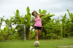 Young happy and excited Asian woman in sport clothes playing football having fun at jungle soccer field with palm trees and grass. In nature and healthy Royalty Free Stock Image