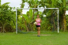 Young happy and excited Asian woman in sport clothes playing football having fun at jungle soccer field with palm trees and grass. In nature and healthy Royalty Free Stock Images