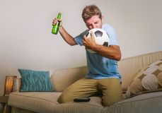 Young happy excited and crazy football fan man celebrating team scoring goal and victory watching game on television kissing socce Royalty Free Stock Images