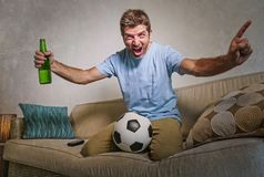 Young happy excited and crazy football fan man holding soccer ball celebrating team scoring goal and victory watching game on tele. Vision screaming spastic Royalty Free Stock Photos