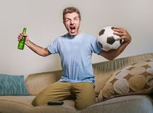 Young happy excited and crazy football fan man holding soccer ball celebrating team scoring goal and victory watching game on tele. Vision screaming spastic Royalty Free Stock Image
