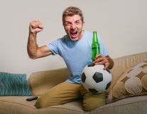 Young happy excited and crazy football fan man holding soccer ball celebrating team scoring goal and victory watching game on tele. Vision screaming spastic Stock Photography