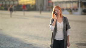 Young happy excited laughing woman talking on mobile phone, girl with red hair waves her hand at the street, city urban. Background., sunny day stock video footage