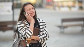 Young happy excited laughing woman talking on mobile phone and girl waves her hand at the street, city urban background. Sunny day stock footage