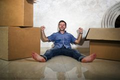Young happy and excited man at home floor enjoying unpacking cardboard boxes moving alone to new apartment or house smiling stock photos