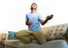 Young happy and excited man jumping on sofa couch listening to m. Usic with mobile phone and headphones playing air guitar crazy having fun at home living room Stock Photography