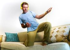 Young happy and excited man jumping on sofa couch listening to m. Usic with mobile phone and headphones playing air guitar crazy having fun at home living room Royalty Free Stock Photo