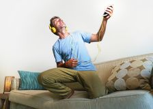 Young happy and excited man jumping on sofa couch listening to m. Usic with mobile phone and headphones playing air guitar crazy having fun at home living room Royalty Free Stock Photography